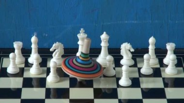 Colorful whirligig  on chessboard with white chessmens — 图库视频影像