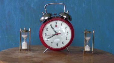 Analog alarm-clock and two sand glass, hourglass on table — Stock Video