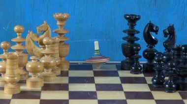 Colorful wooden whirligig  on chessboard with chessmen — Stock Video