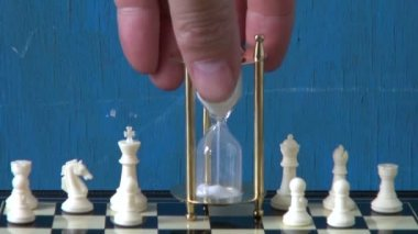 Sandglass on chessboard and white chess — Stockvideo
