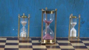 Three sandglass on chessboard — Stock Video