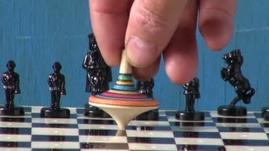 Chess and colorful  wooden toy whirligig on chessboard — Stock Video