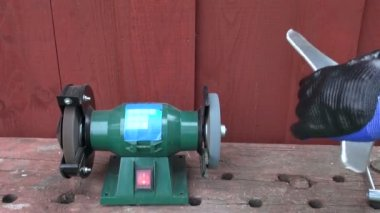 Sharpening grass cutter lawn mower trimmer  blade on stone — Stock Video