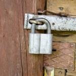 Old padlock on wooden farm barn door — Stock Photo