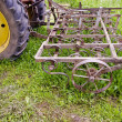 Tractor with old agriculture rake machinery in farm — Stock Photo #35896871
