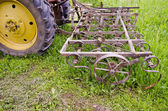 Tractor with old agriculture rake machinery in farm — Stock Photo