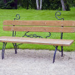 Wooden decorative bench at a park — Stock Photo