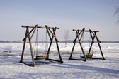Two wooden swings in winter park — Stock Photo
