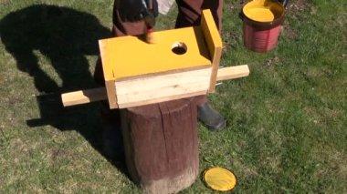 Paint in yellow new bird house nesting-box — Stockvideo