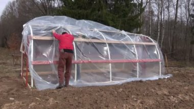 Workers in spring farm make new plastic  greenhouse — Stock Video
