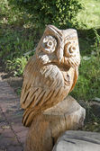 Wooden carved owl in summer garden — Stock Photo