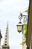 Old street with lamp in Paris and church tower — Stock Photo