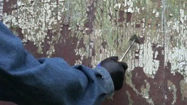 Worker scrapping old cracked paint from wooden door — Stock Video