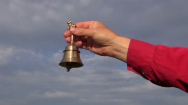 Hand hold ornamental  brass bell on blue sky background — Video Stock