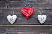 Three cloth heart symbols on old wooden wall — Stock Photo
