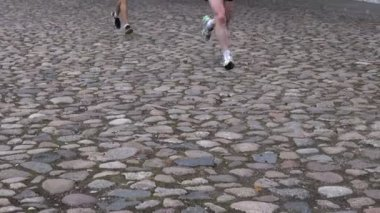 Running race people competing. feet on cobblestone road — Stock Video