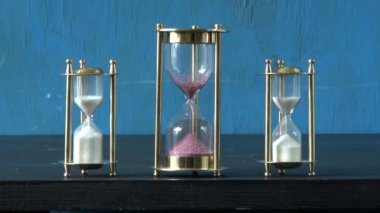 Sand motion in three sandglass, sand clock. — Stock Video