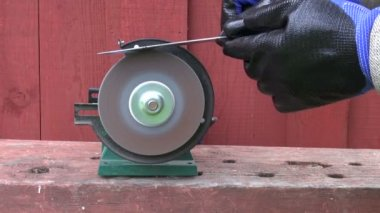 Farmer hands  sharpening knife with electric tool — Wideo stockowe