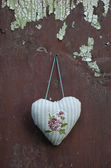 Decorative cloth heart textile hanging on old cracked wall — Stock Photo