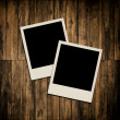 Blank instant photo frames on old wooden background — Stock Photo