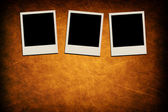 Blank instant photo frames on grunge brown background — Stock Photo
