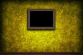 Old wooden frame on yellow retro grunge wall — Stock Photo