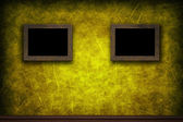 Old wooden frames on yellow retro grunge wall — Stock Photo