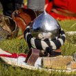 Helmet and shield of the medieval knight on the green field. — Stock Photo