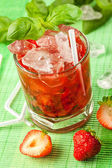 Red drink on a green background and ice — Stock Photo