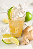 Yellow drink with lime, ginger and ice — Stock Photo