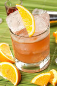 Orange drink on a green background — Stock Photo