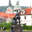 Prague, Czech Republic - May 8, 2013: One of the bronze sculptures in Wallenstein Gardens (Valdstejnska zahrada). In the background is the palace Wallenstein first baroque palace in Prague. — Stock Photo