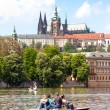 Prague, Czech Republic - May 8, 2013: Vltava river with people floating in boats. In the background - Hradcany. UNESCO. - Photo