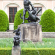 One of the bronze sculptures in Wallenstein Gardens  Valdstejnska zahrada   In the background is the palace Wallenstein first baroque palace in Prague, Czech Republic — Stock Photo