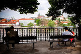 Prague, Czech Republic - May 09, 2013: People sit on the benches on the Vltava riverbank and look at Hradcany castle — Foto de Stock