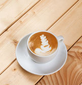 Cappucino with leaf shape foam on wooden table — Stock Photo