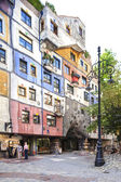 Vienna, Austria - August 30, 2013. Tourists walk around the Hundertwasserhaus Was made by Fredensreich Hundertwasser Und Josef Krawina. Colored building. — Stock Photo