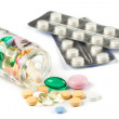 Multi color pills spills out of the little jar, bottle, two blisters of pills, isolated on white — Stock Photo #38862251