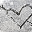 Heart pierced by an arrow drawn with the snow — Stock Photo #39642449