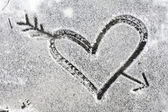 Heart pierced by an arrow drawn with the snow — Stock Photo
