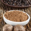 Spice nutmeg in whole and ground in a white bowl, black pepper — Stock Photo #39925695