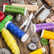 Scattered sewing spools and buttons, scissors and needles — Stock Photo