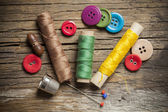 Set of colored sewing buttons and bobbin threads on wooden background — Stock Photo