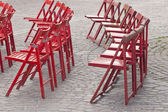 Red wooden chairs on cobble street — Stock Photo