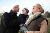 Parents with young children gaze up in amazement — Stock Photo