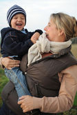 Laughing boy on his mother's arm — Stock Photo