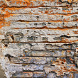 Grunge texture of old brick with plaster crumble - Stock Photo