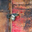 Old padlock on the door of the barn - Stock Photo