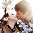 Spring outdoor portrait of a young couple kissing - Stock Photo