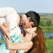 Summer outdoor portrait of a young couple kissing - Stock Photo